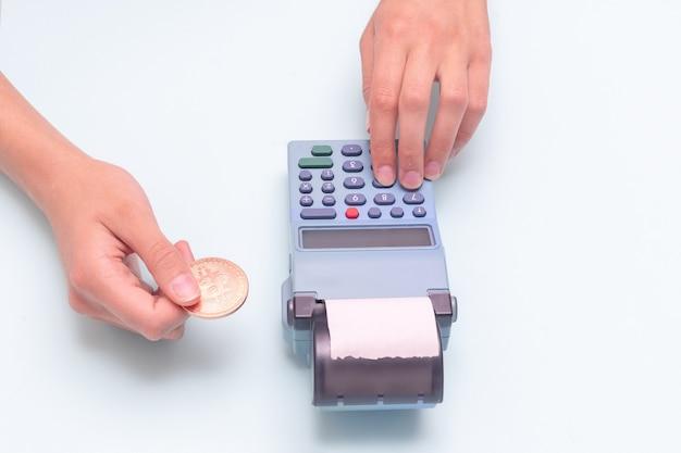 Оплата покупок электронными деньгами, биткойнами, e-commerce. крупный план руки, держащей монету биткойн и руки, вводящей сумму, считая в кассовом аппарате на синем фоне.