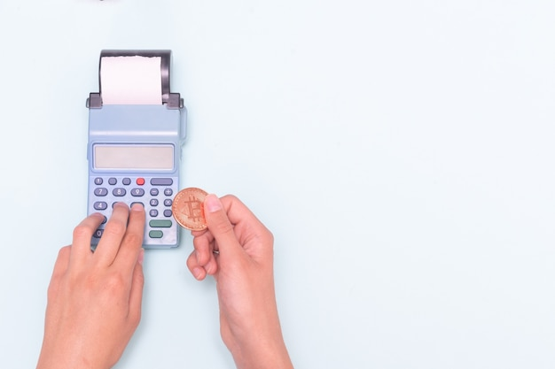 電子マネー、ビットコイン、eコマースでの購入の支払い。ビットコインコインを持っている手のクローズアップとレジで数えて金額を入力している手。ビジネスコンセプト、オンライン販売。