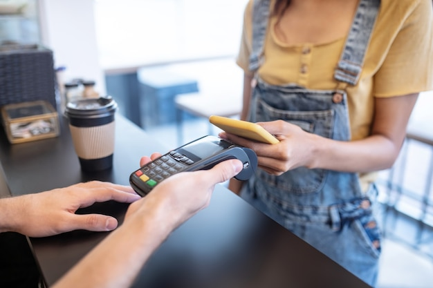 Платежное поручение. женские стройные руки держат желтый смартфон возле плаката над прилавком в кафе