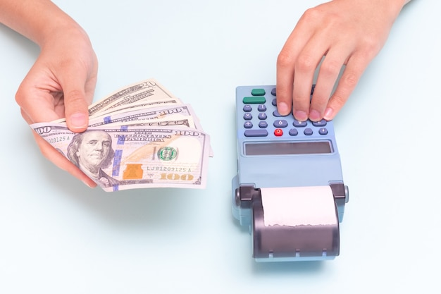 Payment for purchases in cash, dollars. close-up of a hand giving cash and hand typing the amount, counting at the cash register against a blue background. business concept, retail, online sale.