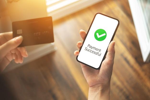 支払いが成功し、クレジットカード、スマートフォンを持った女性がオンラインで注文またはインターネットで購入、銀行および転送技術のコンセプト写真