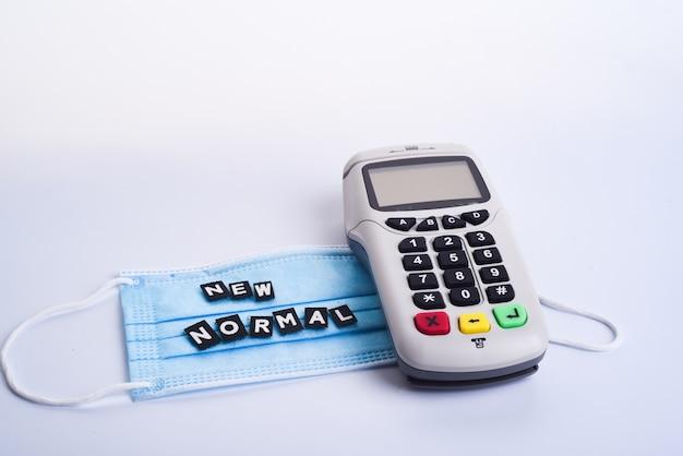Безналичный платежный терминал на белом фоне. касса. pos-терминал. банковское оборудование. приобретение. интернет-банкинг. изображение coronavirus- covid-19 или 2019-ncov. медицинская маска.