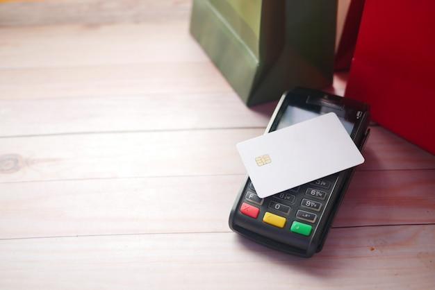 테이블에 쇼핑백이 있는 카드에서 충전하는 결제 단말기
