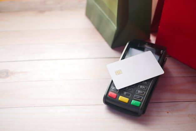 Payment terminal charging from a card with shopping bag on table