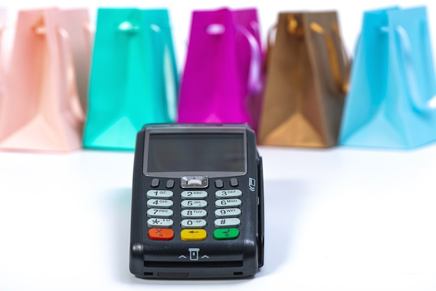 Payment terminal and colourful paper bags isolated on bright surface, contactless payment concept