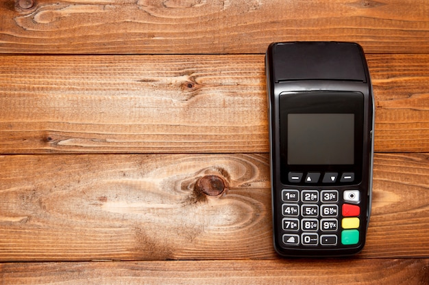 Payment terminal, compact pos terminal on wooden background