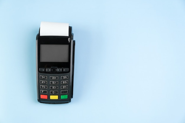 Платежный терминал pos с рулонной наличной лентой на синем фоне с копией пространства