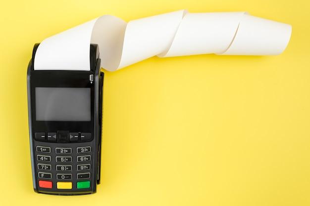 Платежный терминал pos с рулонной наличной лентой на желтом фоне с копией пространства
