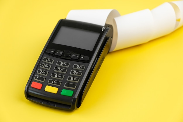 Payment terminal pos with a roll cash tape on the yellow background