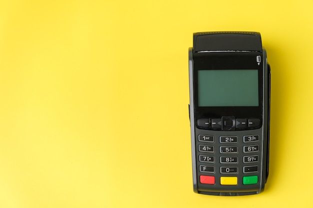 Payment terminal pos on the yellow background with copy space