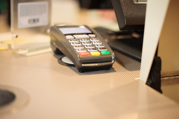 Payment terminal on the table at huge shopping center