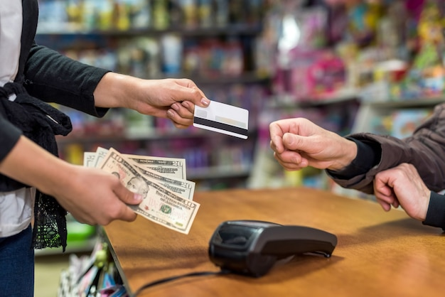 Payment in toy shop with dollars and credit card