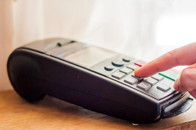 신용 카드-포스 터미널을 들고 사업가와 지불. 은행 터미널의 결제 카드. 전자 지불의 개념. 카드 기계 또는 pos 터미널의 핀 패드에 핸드 핀 코드