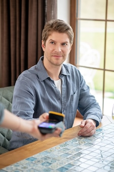 Payment. young adult smiling man holding smartphone to portable pos terminal to pay check in restaurant