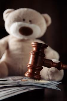 Выплаты алиментов. деревянный молоток судьи, денежные банкноты и крупный план плюшевого мишки. понятие развода.