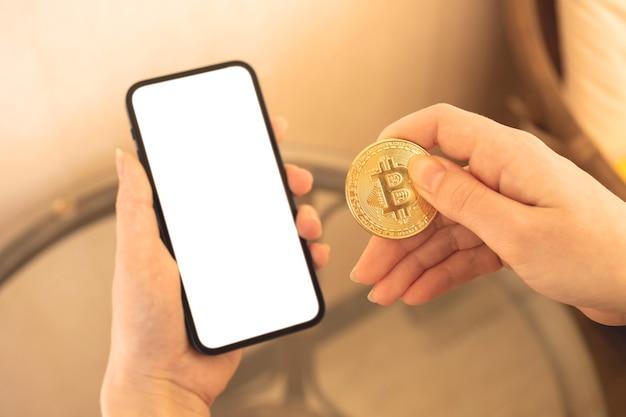 Платежи с помощью макета криптовалюты, мобильного телефона с пустым белым экраном и женской руки с золотой биткойн-монетой, копией космического фото