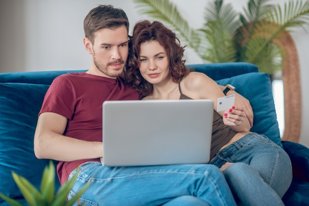 オンラインでの支払い。オンラインで何かを購入することを計画している若いかわいいカップル