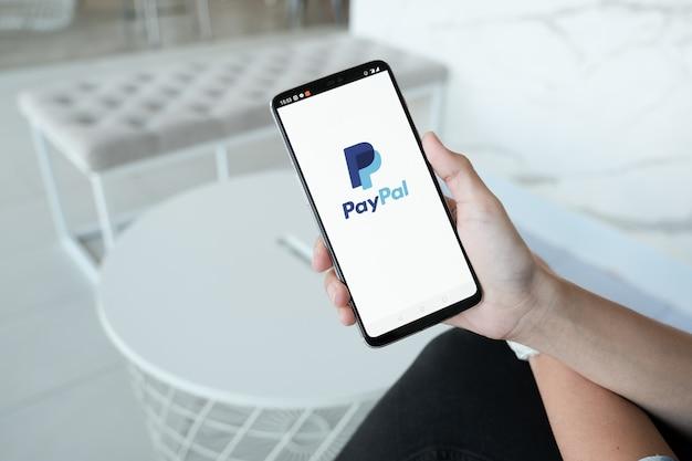 画面上のpaypalアプリでスマートフォンを保持している女性の手。 paypalは、オンラインの電子決済システムです。