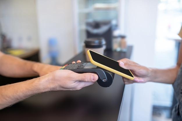 Paypass. мужские руки держат черный pos-терминал, а женщина приносит смартфон, лица не видны