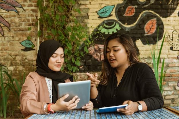 タブレットpcを使用して2つのアジアの女の子