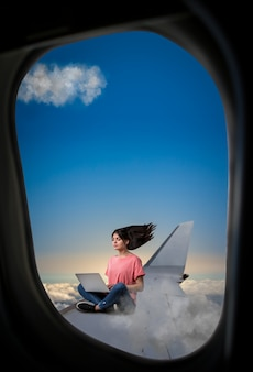 Pc addiction, woman with laptop sitting on plane wing, view from airplane porthole