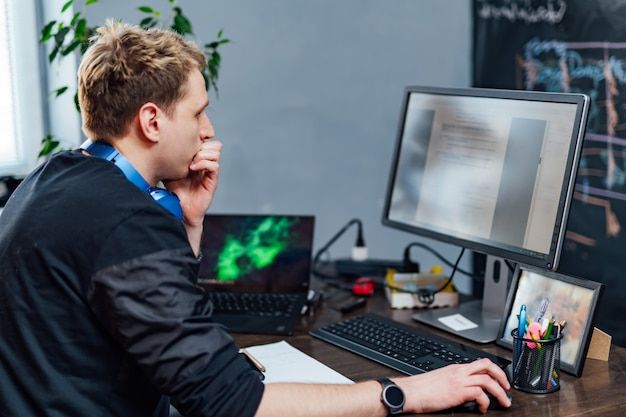 深刻な若者は、pc画面の問題に集中しました。スマートプログラマーはit会社で屋内で一生懸命働いています。