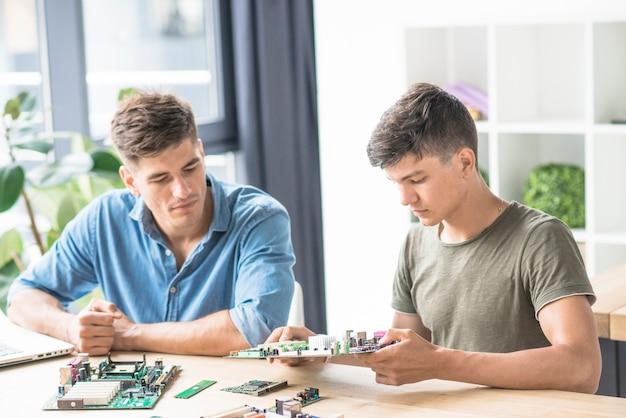 Pcマザーボードを修理するitエンジニアを見ている同僚