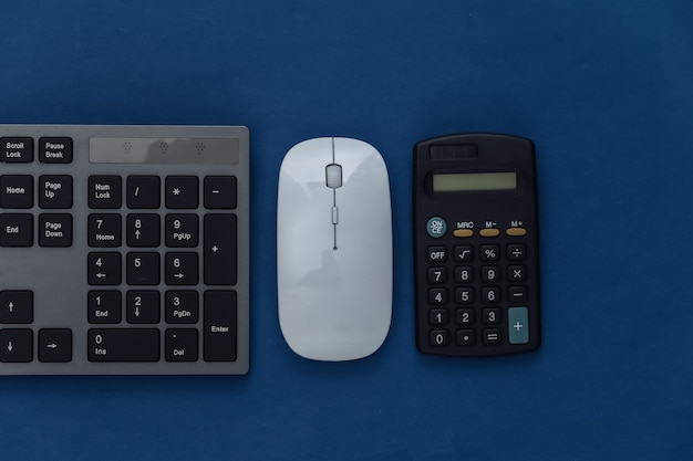 Pc keyboard, mouse and calculator on a classic blue