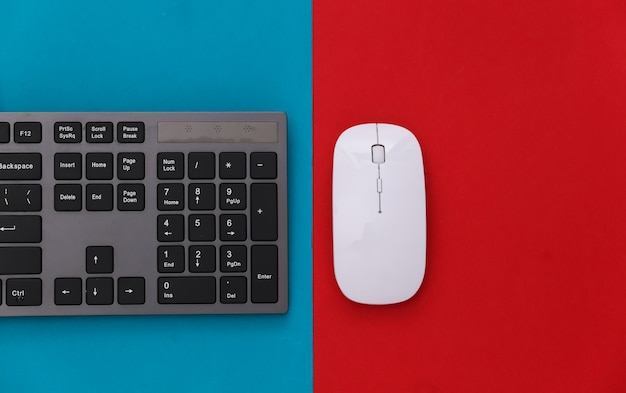 Pc keyboard and mouse on red blue