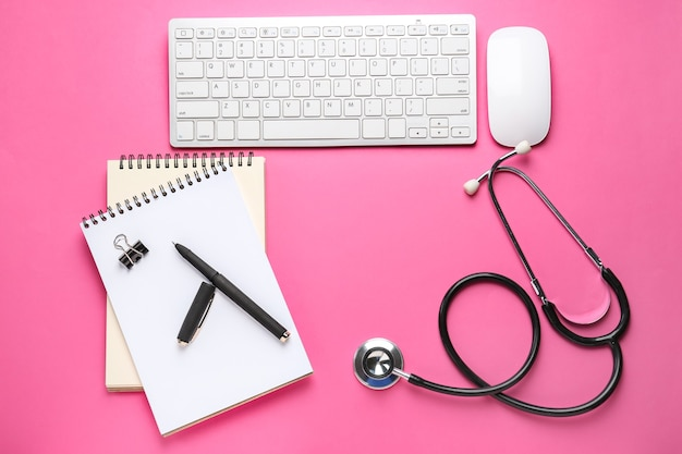 Pc keyboard, mouse, stethoscope and stationery on color background