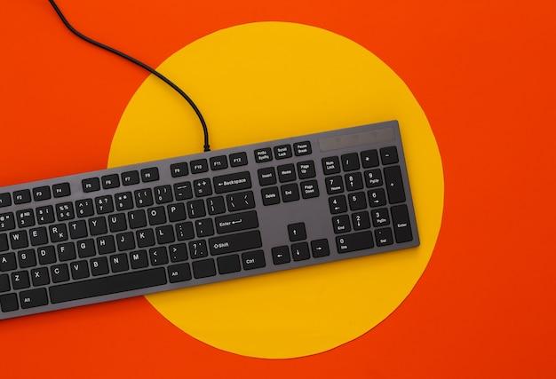 Pc keyboard on orange with yellow circle