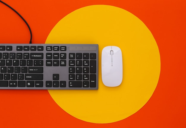 Pc keyboard and pc mouse on orange with yellow circle