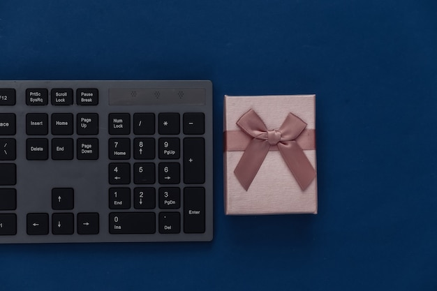 Pc keyboard with gift box on a classic blue