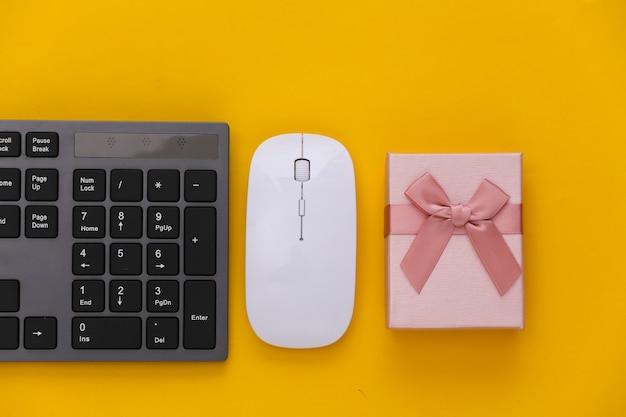 Pc keyboard with gift box on yellow