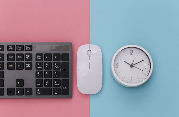 Pc keyboard with pc mouse, clock on pink blue