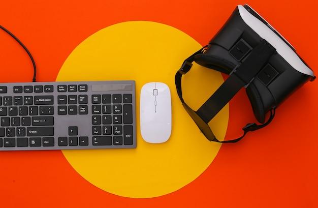 Клавиатура пк с шлемом vr на цветном столе. современные гаджеты. виртуальная реальность