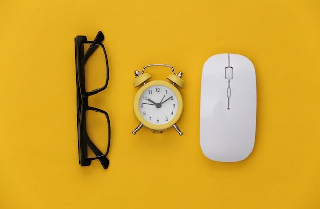 Компьютерная мышь, очки и будильник на желтом фоне. офисные принадлежности.