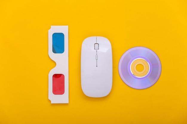Компьютерная мышь с анаглифическими очками 3d, компакт-диск на желтом фоне. развлечение. вид сверху