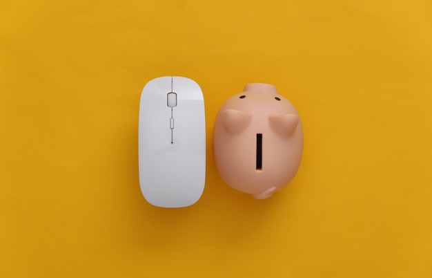 Pc mouse with piggy bank on yellow background. online business. top view. minimalism