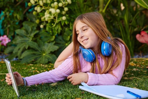 タブレットpcの芝生の上で金髪の子供女の子selfie写真