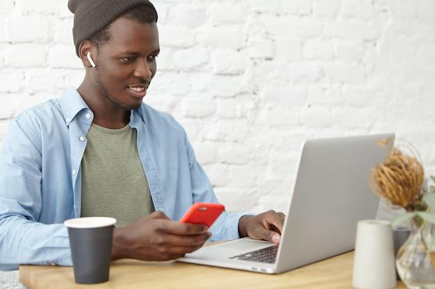 ラップトップpcでビデオまたはシリーズをオンラインで見ながら、ワイヤレスのイヤフォンを使用して帽子のトレンディな笑顔の若い浅黒い肌の男、カフェのテーブルに座って、携帯電話でsmsを送信してコーヒーを飲む