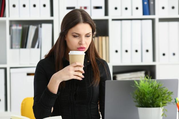 美しいブルネットの笑みを浮かべて店員女性はラップトップpcコンピューターで動作しますお茶の肖像画の腕プラスチックカップを保持します。ホワイトカラー店員労働者職場の仕事提供webチャットワイヤレスソーシャルネットの概念