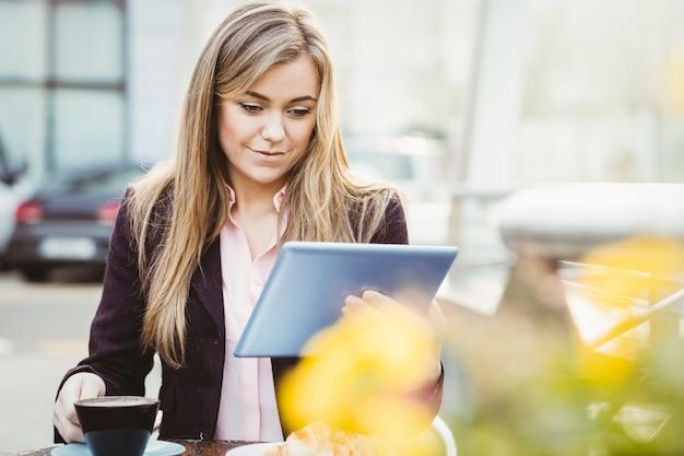 カフェで彼女のタブレットpcを使用して実業家