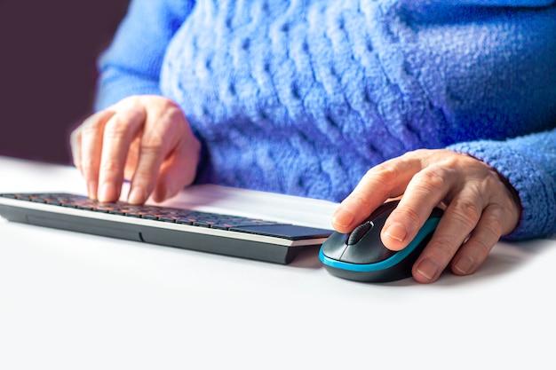 Pcのキーボードで入力する高齢者の女性の手をクローズアップ。在宅勤務の年金受給者。コンピューターリテラシーまたはインターネットスキルの高齢者を学習する概念。