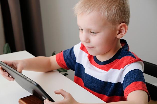 オンライン教育の遠隔学習。自宅でタブレットpcで宿題をしているかわいい白人少年