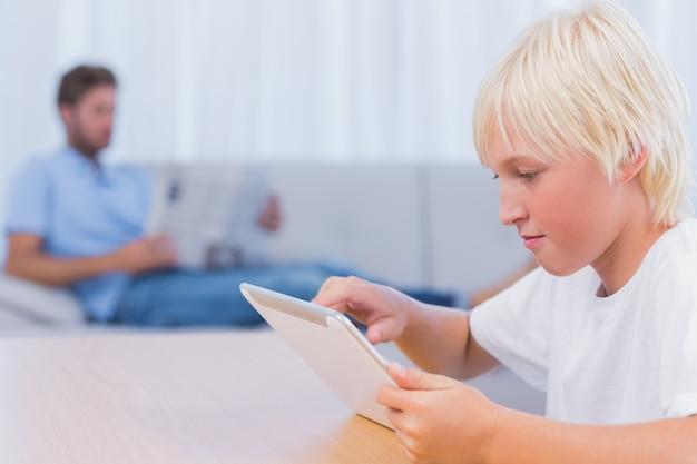 父親が読んでいる間にタブレットpcを使っている少年
