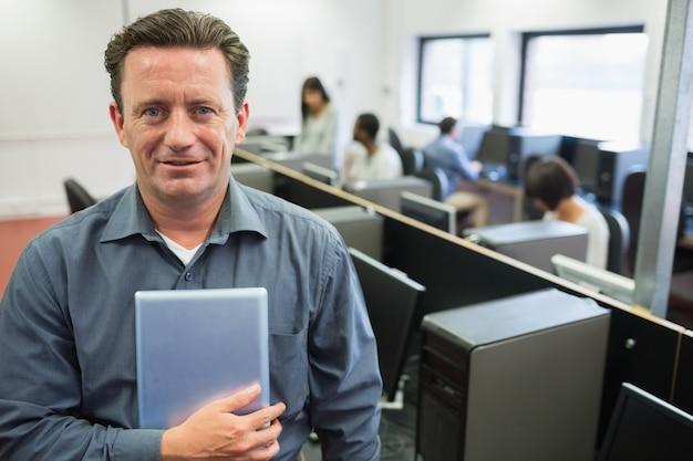 コンピュータルームにタブレットpcを持って、笑っている男