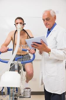医者、フィットネステストをしている男にタブレットpcを示している