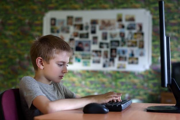 Pcに座っている少年。家庭教育