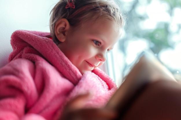 窓枠に座ってタブレットpcを使用してピンクのバスローブでかわいい女の子。